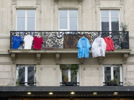"In this picture taken on November 27, 2015 T-shirts and coats hang on a balcony in Paris, in arrangements to re-create the tri-colours of the French national flag in memory of the 130 victims of the November 13, 2015 coordinated terror attacks in Paris claimed by the Islamic State group (IS). A solemn ceremony was held for the victims of the Paris attacks, with President Francois Hollande vowing that France would respond to the ""army of fanatics"" with more songs, concerts and shows. ""We will not give in either to fear or to hate,"" said Hollande in the courtyard of the Invalides buildings in central Paris, speaking to 2,000 dignitaries and those injured in the violence. AFP PHOTO/ ALAIN JOCARD / AFP / ALAIN JOCARD"