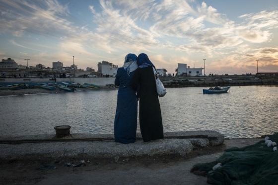 Deux filles regardent le coucher du soleil depuis le port de la ville de Gaza.
