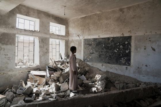 Un enfant dans sa classe détruite au Yémen